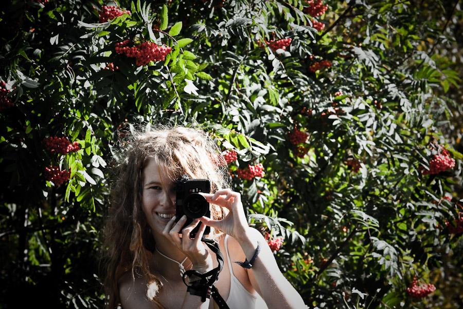 Girl posing holding an old rangefinder camera