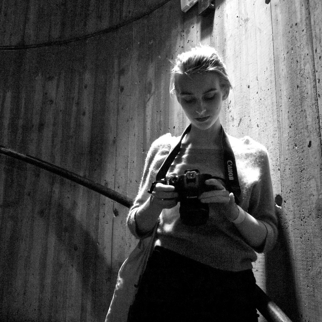 Girl holding a canon camera in a staircase